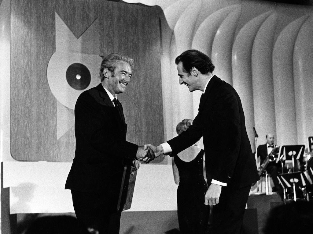 Sur une scène, l'auteur-compositeur québécois Félix Leclerc serre la main de l'auteur-compositeur québécois Gilles Vigneault en 1965.