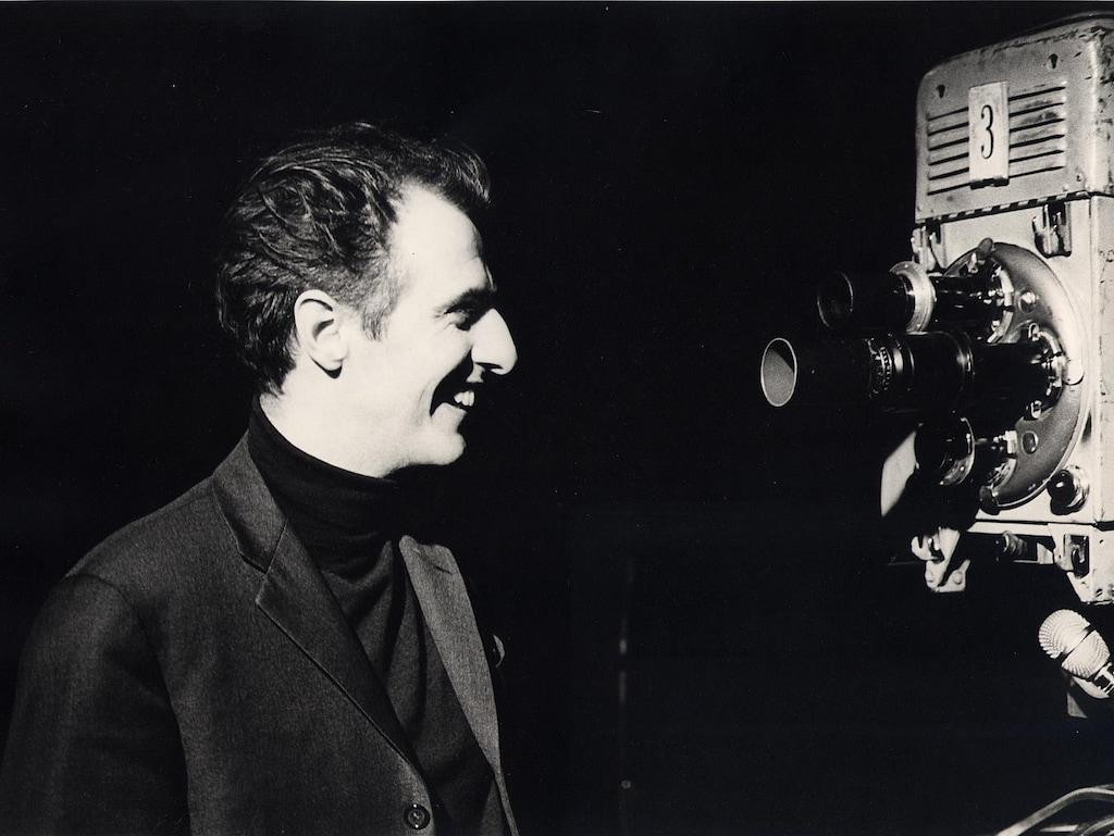 Gilles Vigneault en 1966 regarde une caméra en souriant.