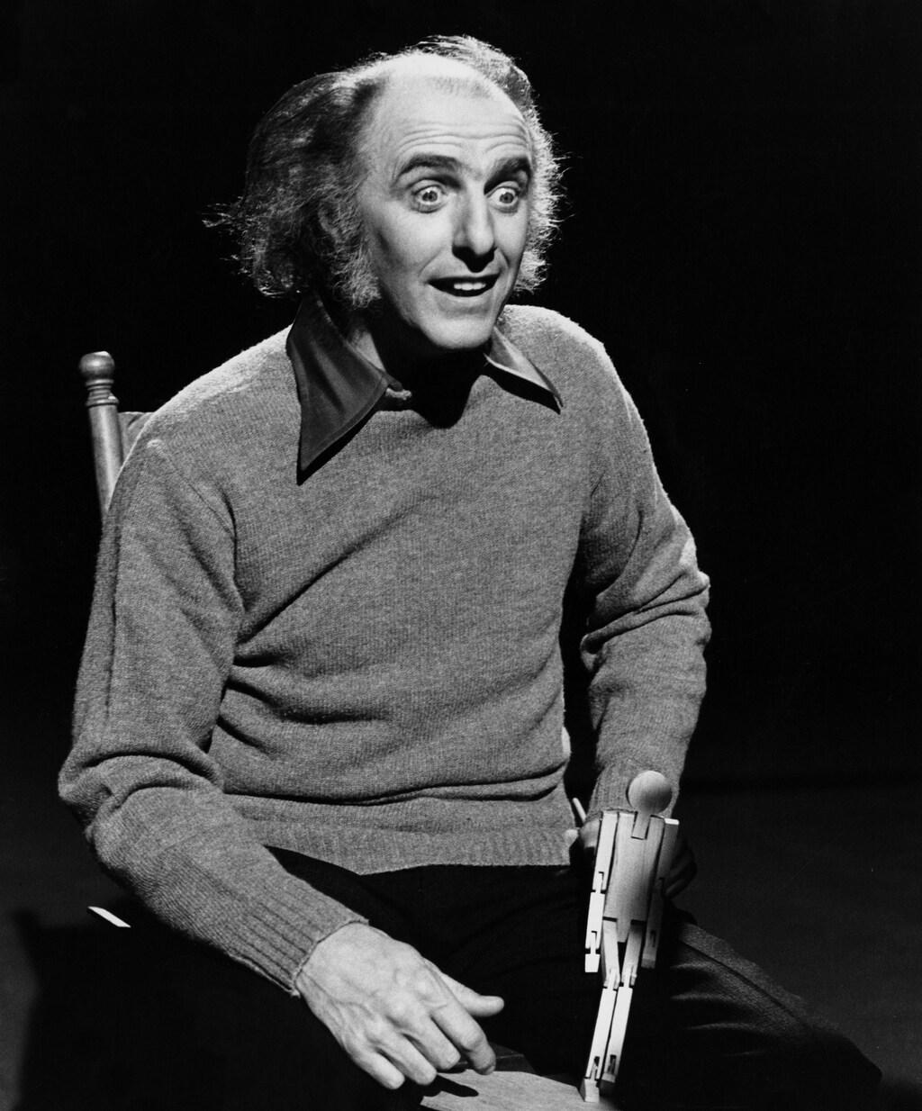 Dans un studio de télévision, l'auteur-compositeur québécois Gilles Vigneault est assis sur une chaise et fait giguer un petit pantin de bois au rythme de la musique.